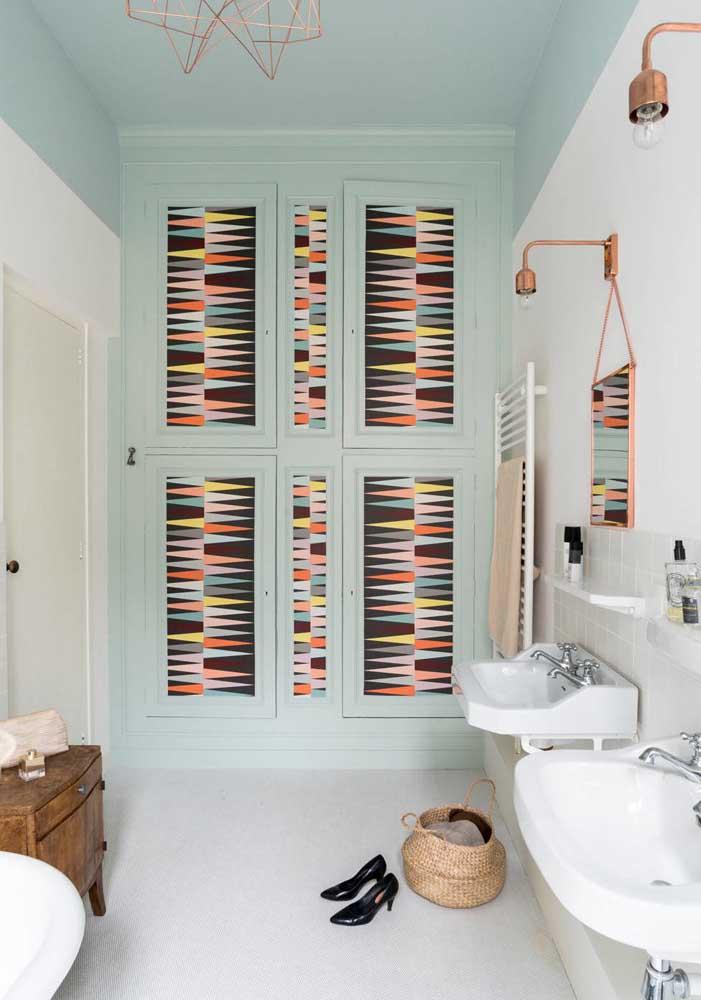 Por aqui, o armário de portas coloridas fica aos fundos do banheiro