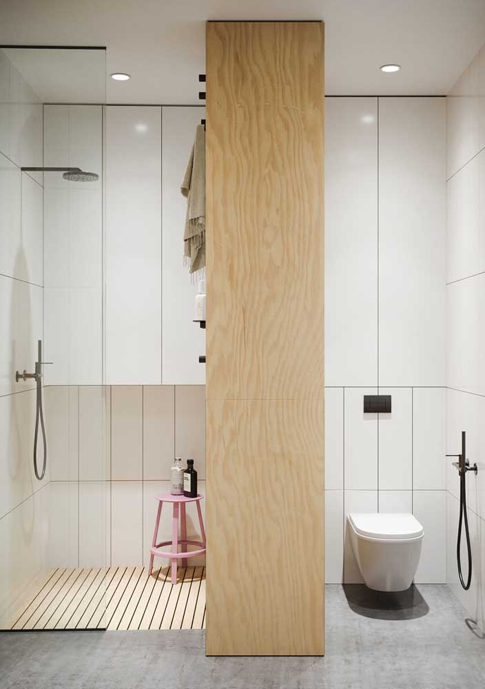 Um armário que também funciona como divisória entre os espaços do banheiro