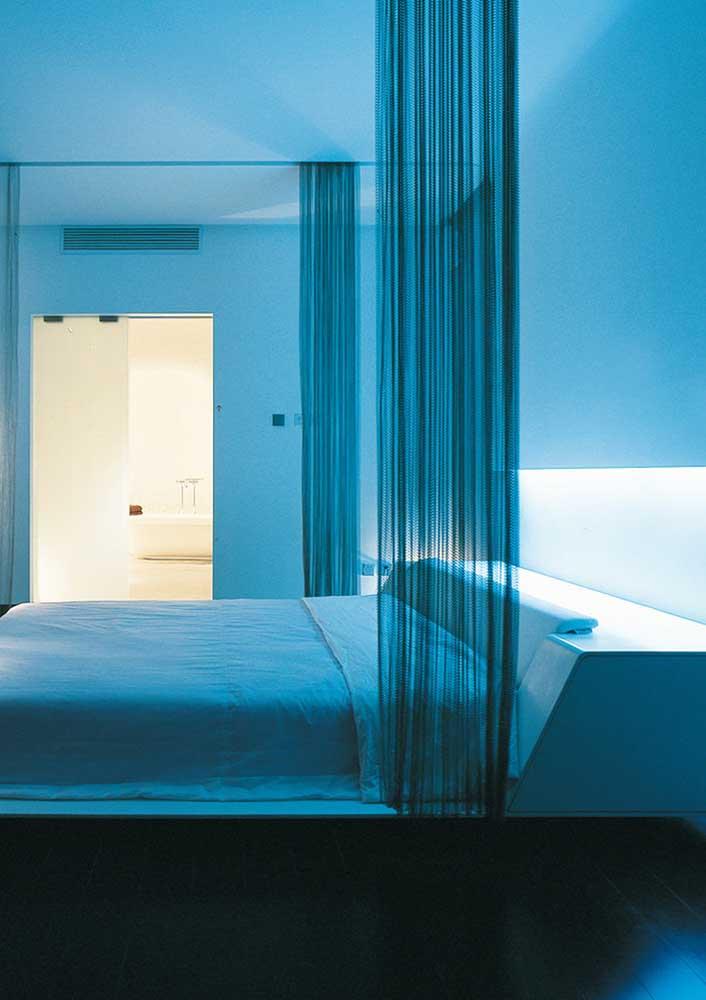 A cortina em torno da cama deixa o quarto mais aconchegante