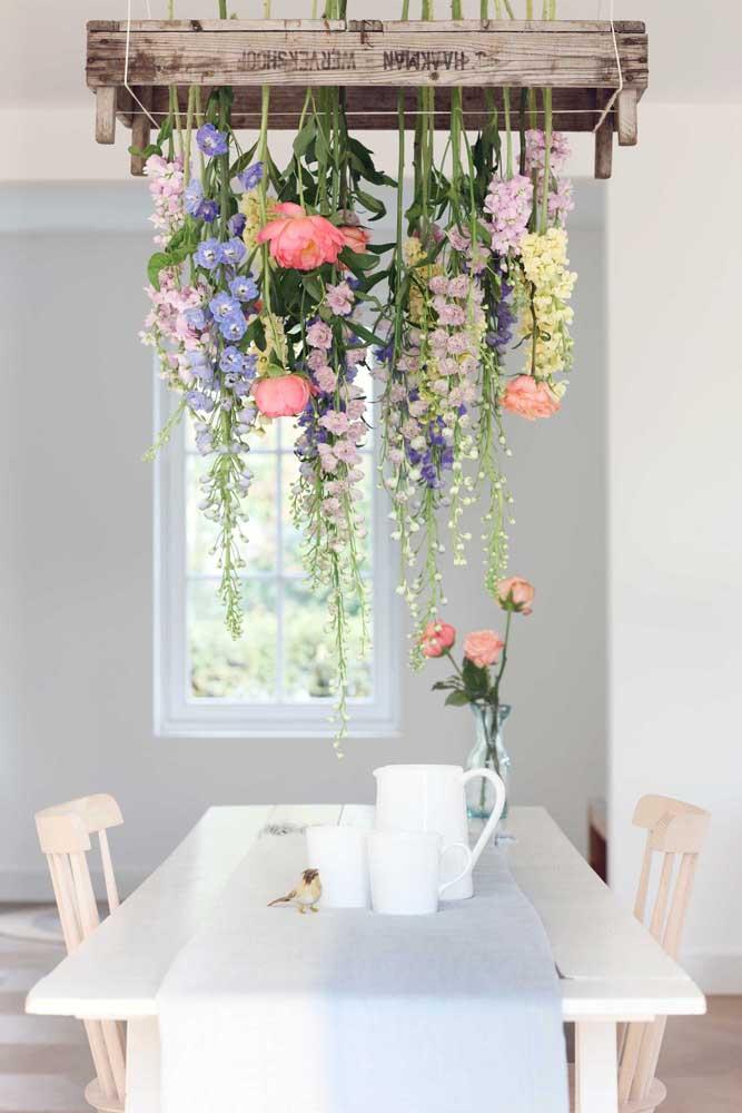 Sala de jantar decorada com uma luminária de flores. É lindo ou não é?