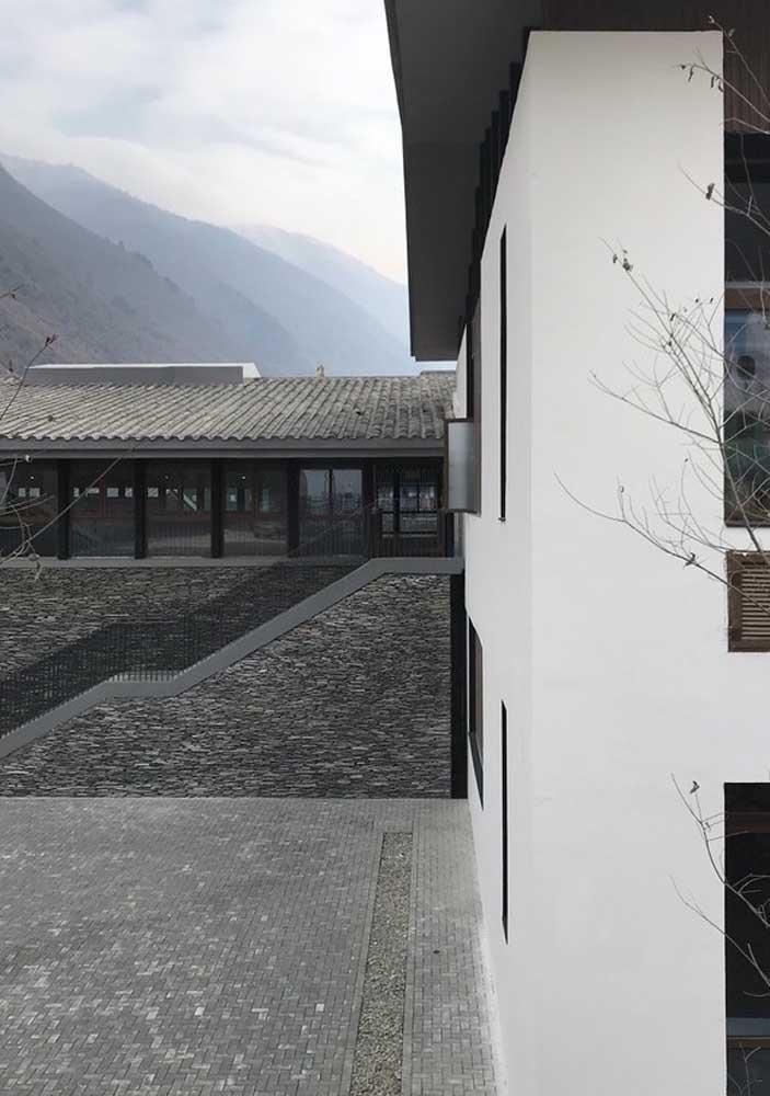Para combinar com o revestimento de pedra use piso intertravado cinza