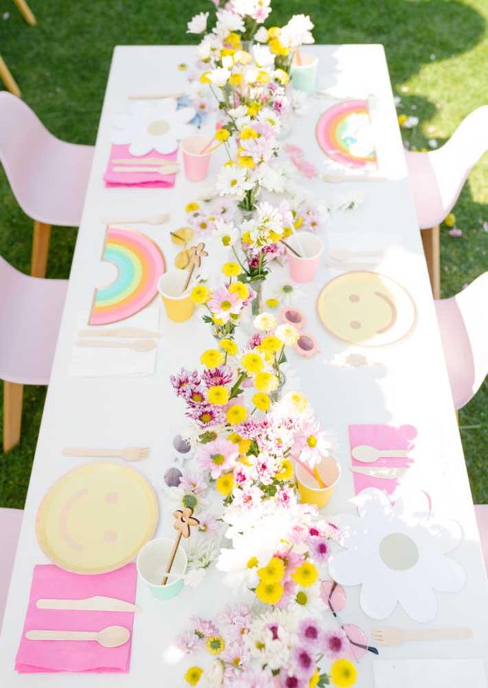 Flores, arco íris e smiles decoram a mesa