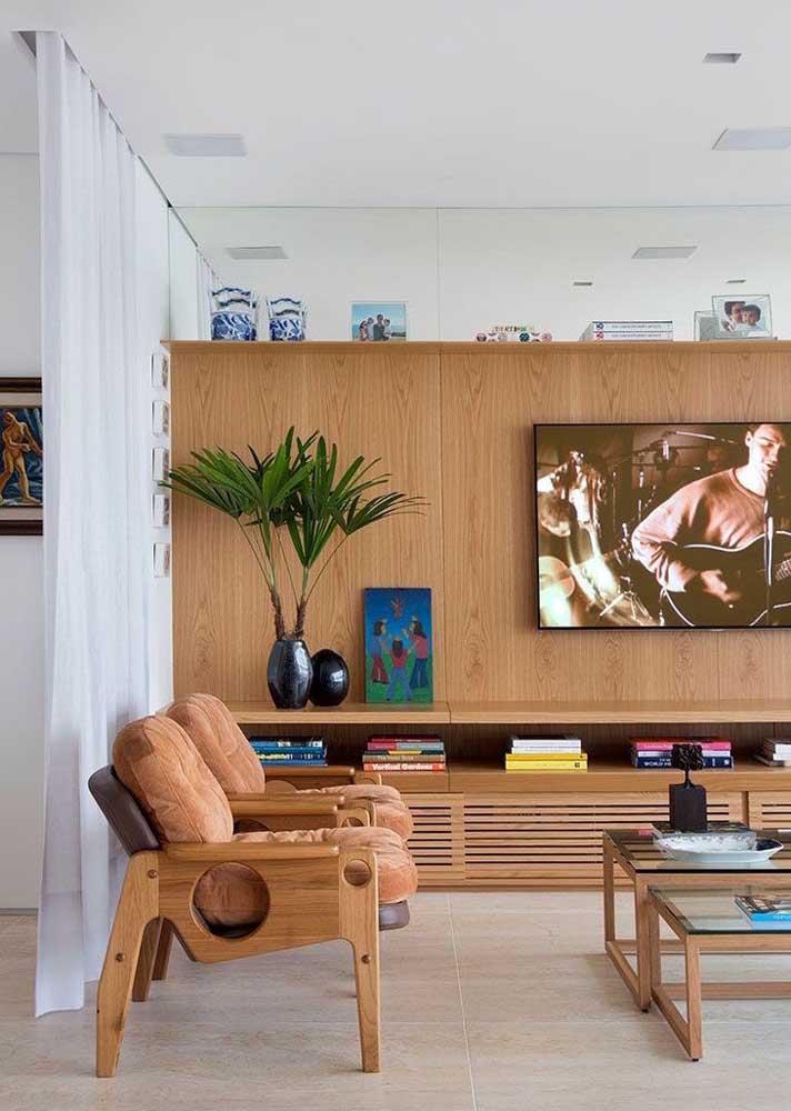 Painel de madeira para sala com rack ocupando toda expansão da parede. Note que a parte de cima é espelhada