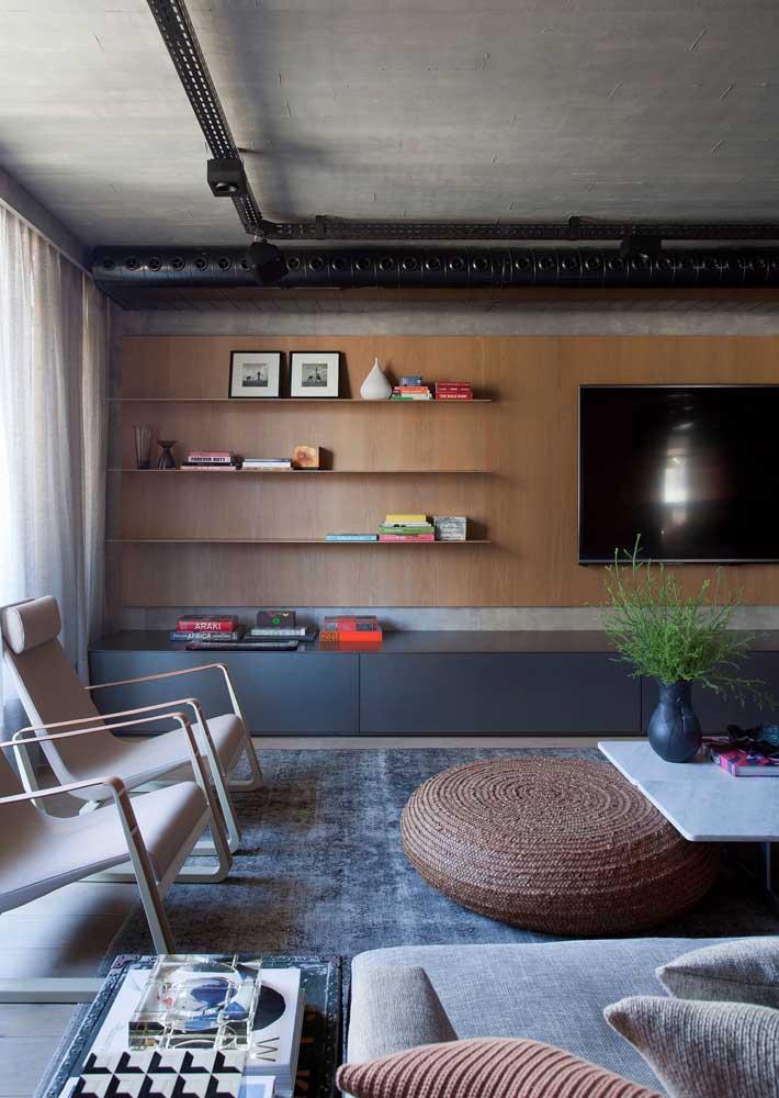 Aqui, o painel de madeira traz conforto e aconchego em contraste com a parede de cimento queimado