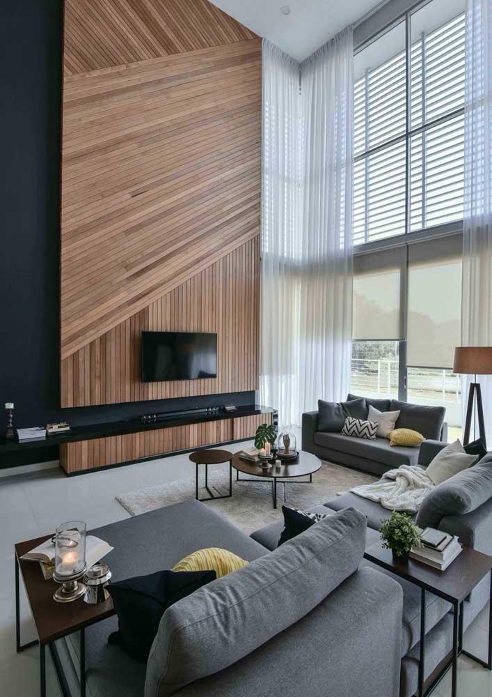 O painel de madeira ripado é o grande destaque dessa sala de pé direito alto
