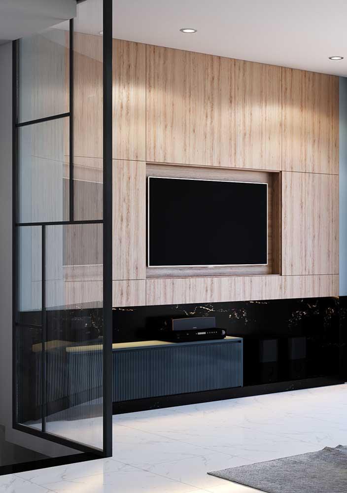 Aqui, o painel de madeira clara e simples ocupa toda a extensão da parede