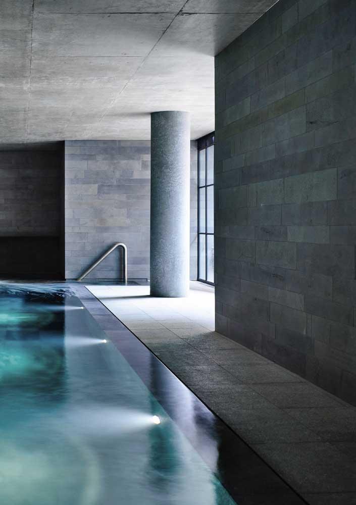 Nessa piscina coberta, o granito se estende para além do piso