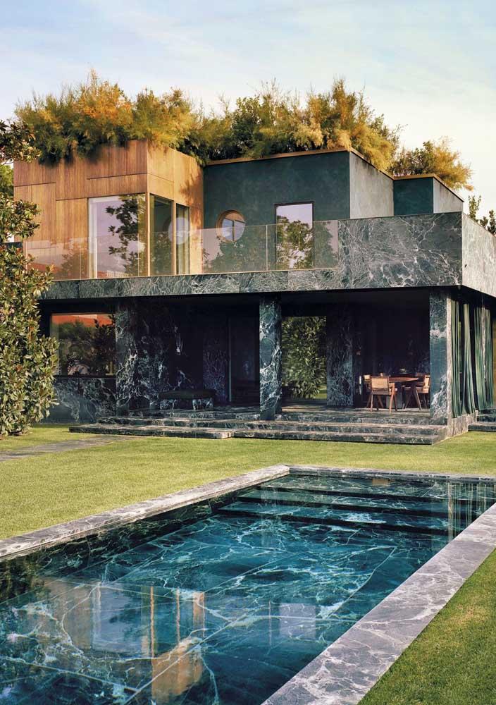 Aqui, o mesmo mármore que foi usado na fachada da casa aparece em torno da piscina