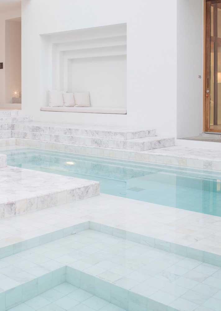 O mármore branco confere uma elegância única para a área da piscina