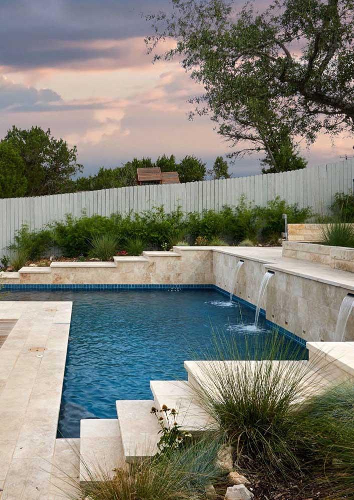 O jardim rústico complementa o visual do piso de pedra para piscina