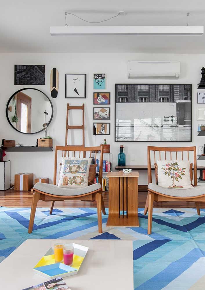 Nessa sala, o padrão geométrico do tapete se repete na bandeja em cima da mesa
