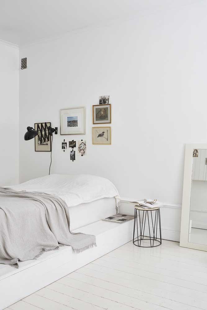 Quarto minimalista com composição de quadros Tumblr na parede da cabeceira