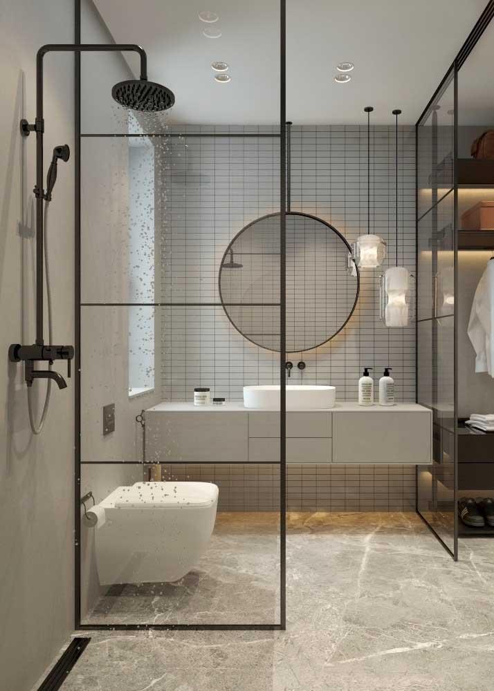 Banheiro cinza e branco com detalhes em preto. Aqui, o cinza entra em diversos tons, do revestimento na parede ao gabinete da pia
