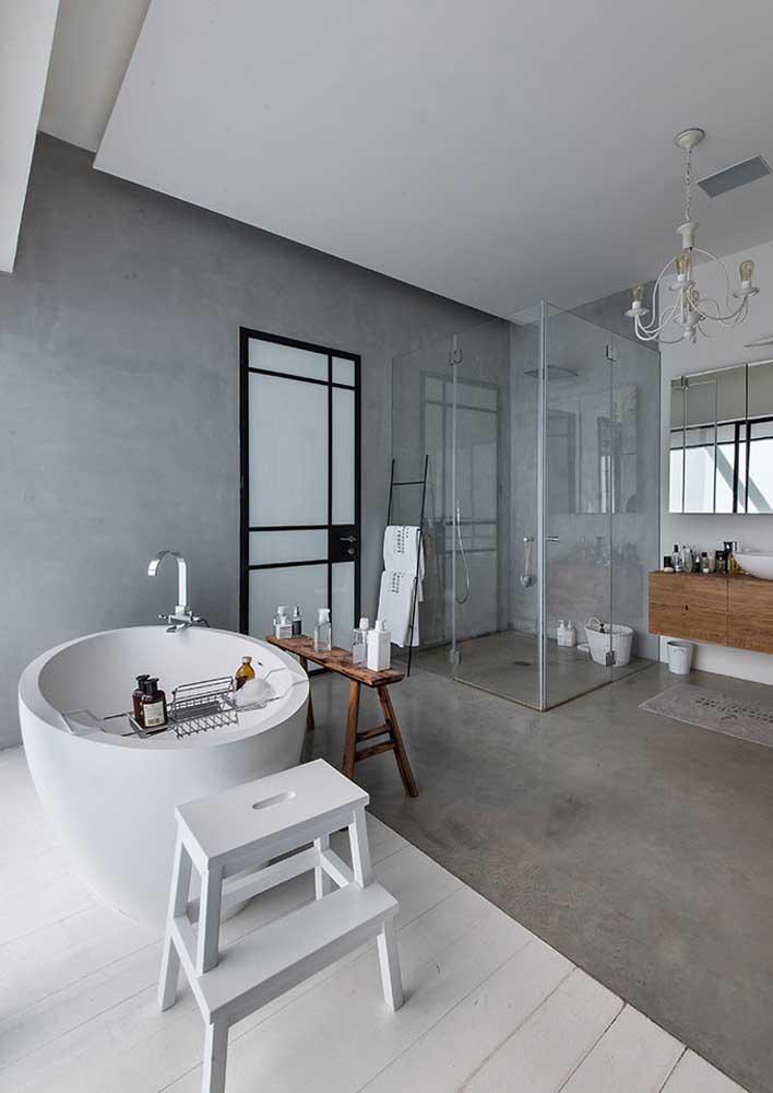 Banheiro cinza moderno e elegante. Repare que o cimento queimado utilizado no piso se harmoniza com o revestimento da parede