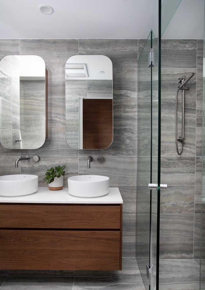 Banheiro cinza com madeira. Aqui, o destaque é o uso da cerâmica que simula um efeito amadeirado