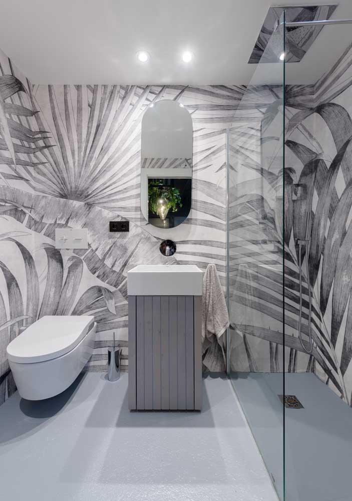 Um banheiro cinza que é pura inspiração! Aqui, a cor entra de modo suave, mesclado ao branco e se destaca no papel de parede