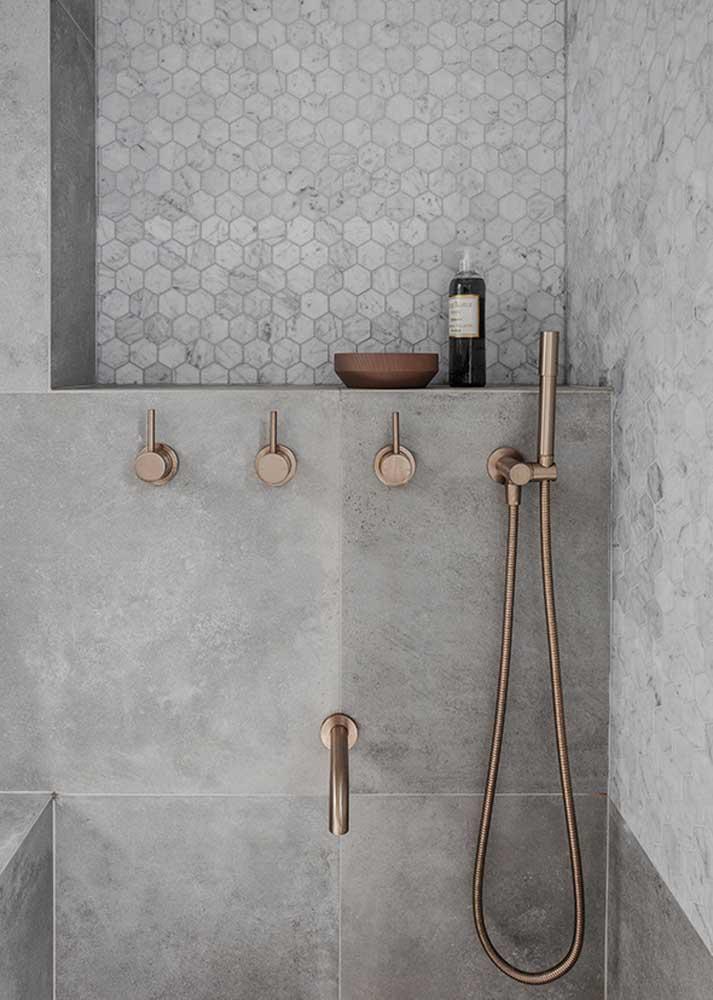 Que tal glamorizar um pouco o banheiro cinza? Para isso, aposte em acessórios metálicos em rosé gold ou dourado