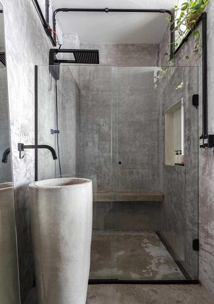 Nesse banheiro o cinza vem do aspecto rústico dos revestimentos, como o cimento queimado