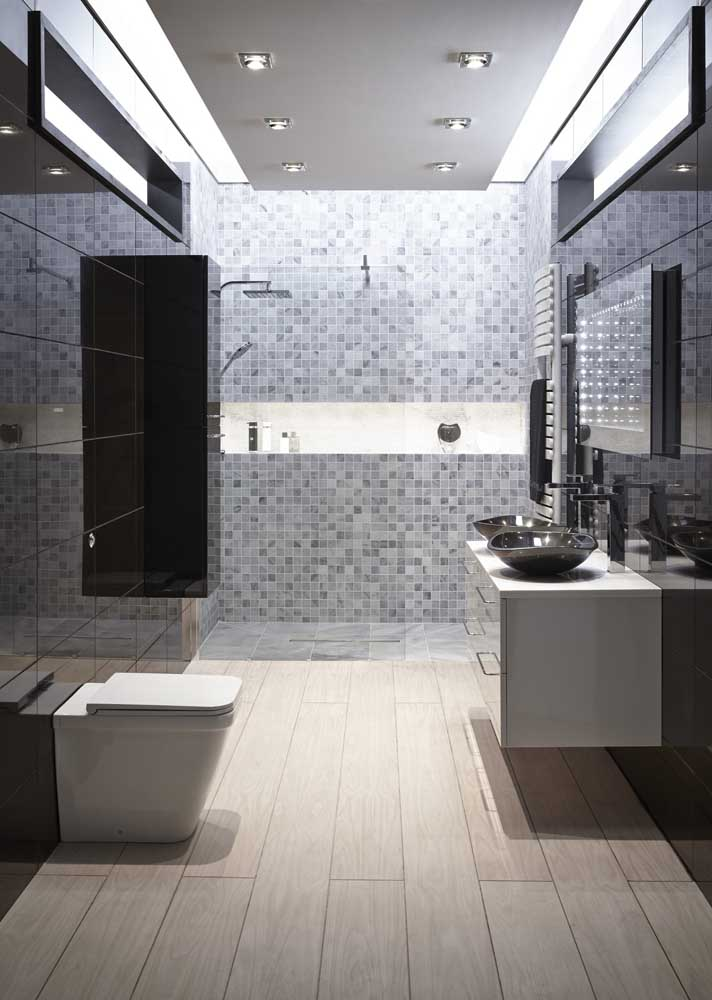 Banheiro cinza com pastilhas na área do box. Para o piso, porcelanato amadeirado