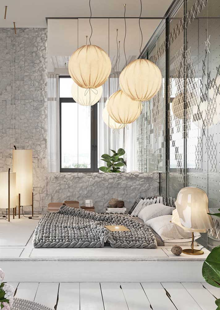 Decoração de quarto de casal em estilo japonês. A cama baixa e as luminárias de papel revelam a influência