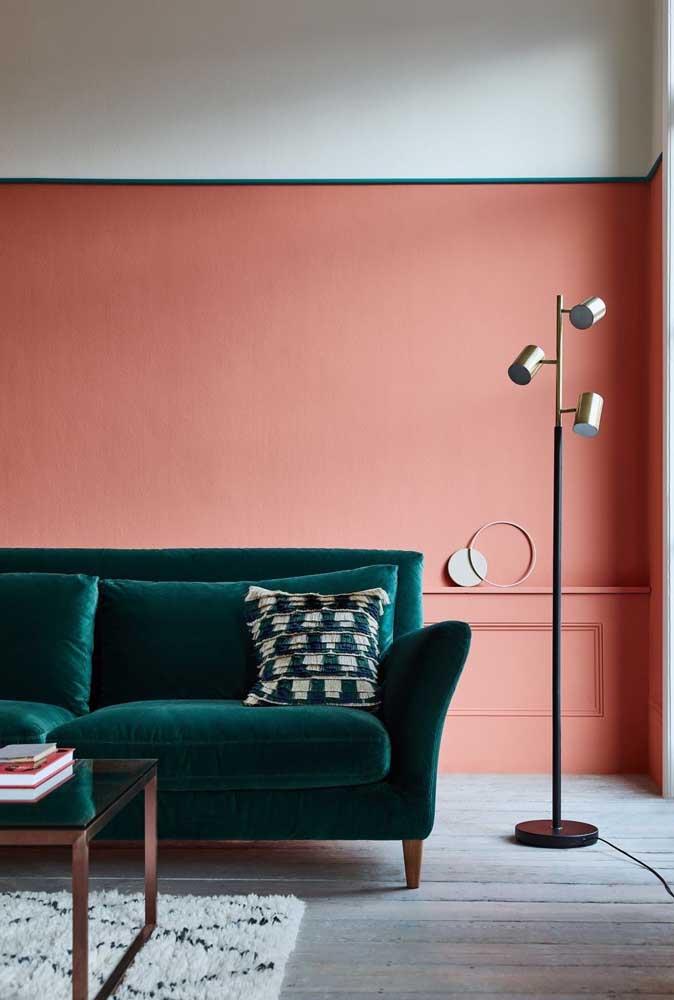Na sala, a opção foi pelas cores complementares: rosa na parede e verde no sofá