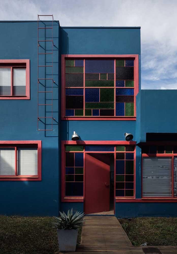 Fachada azul em contraste com as janelas avermelhadas