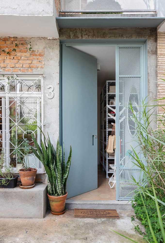 A pintura cinza da porta complementa o tom quente dos tijolinhos