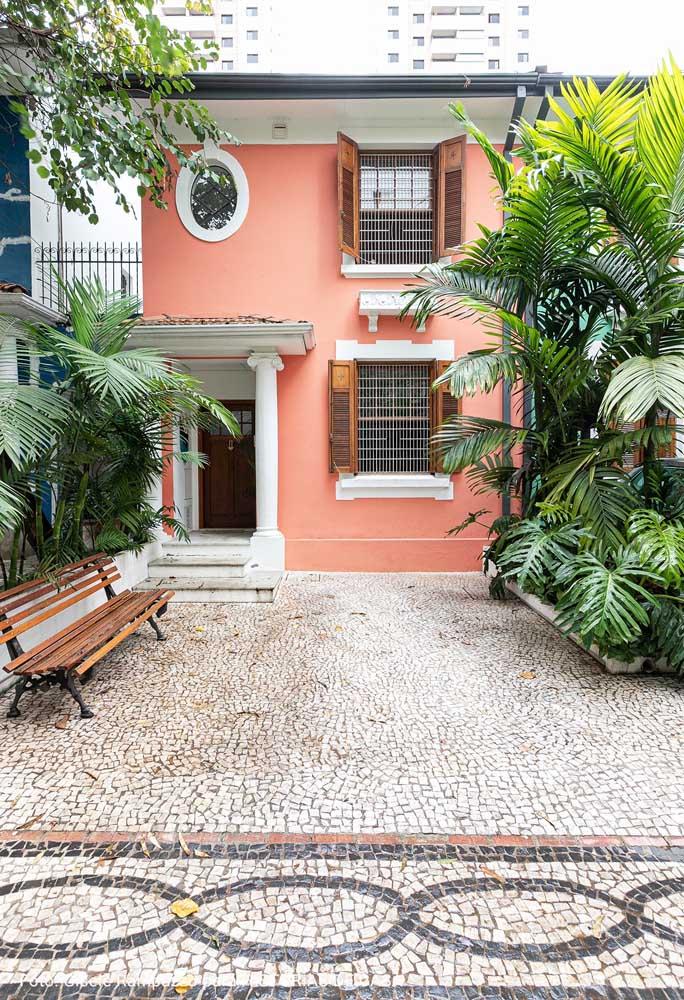 O verde das plantas forma uma companhia perfeita para fachada cor de damasco