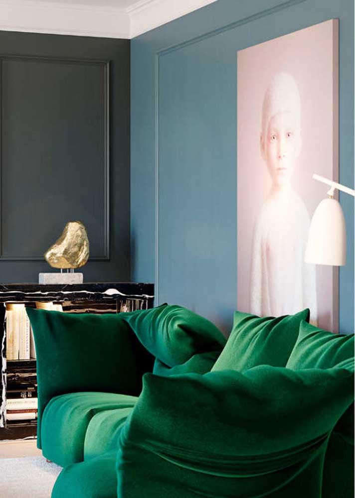 Combinação chiquérrima entre o sofá verde esmeralda e a parede azul. Aos fundos, a parede preta fecha a decoração