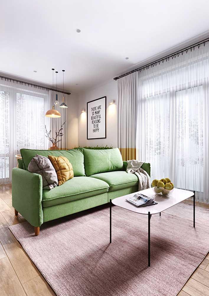 A base branca da decoração garantiu o destaque do sofá verde claro