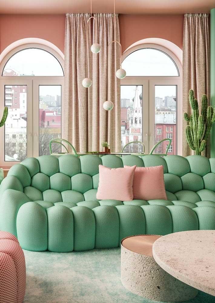 E é claro que em cima do sofá tem uma dupla de almofadas cor de rosa