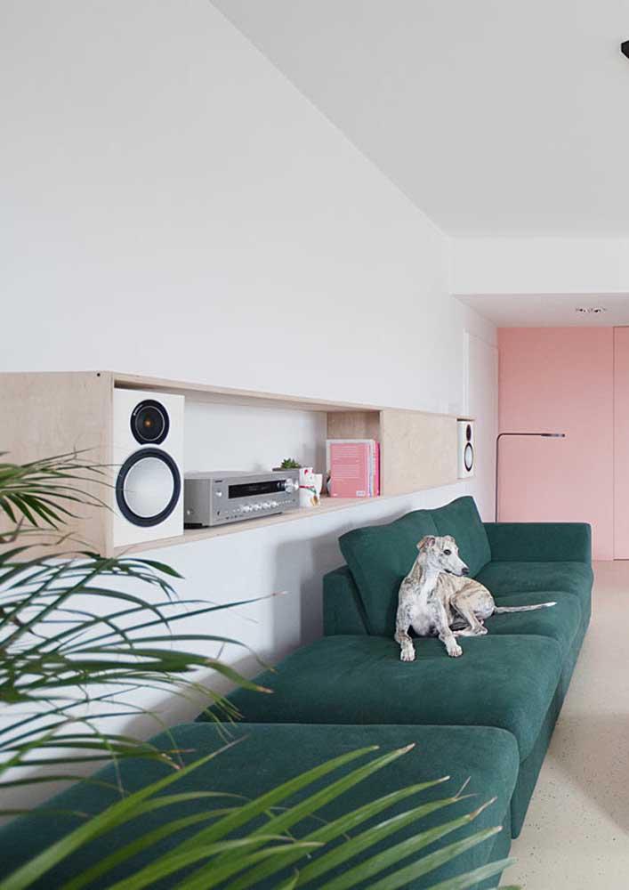 Aqui, o sofá verde se completa com a parede rosa aos fundos