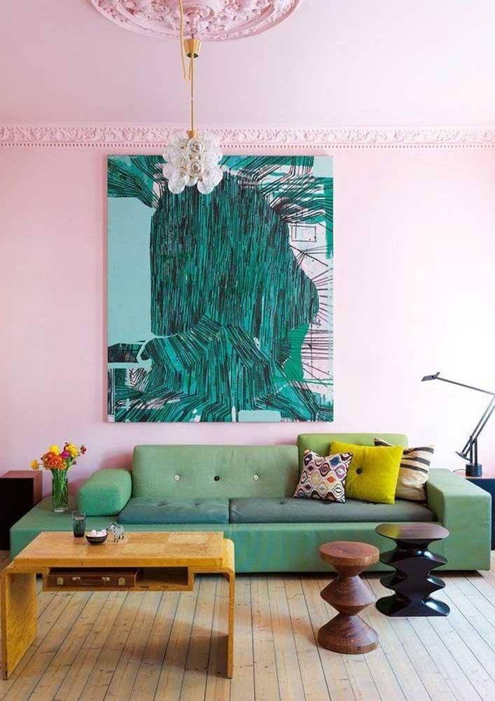 A parede rosa recebeu muito bem o sofá verde claro em companhia das almofadas coloridas