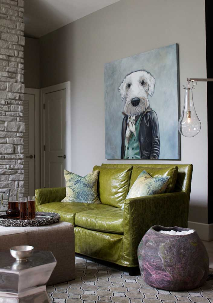 Já aqui, a sala de tons neutros apostou em um sofá verde oliva de couro