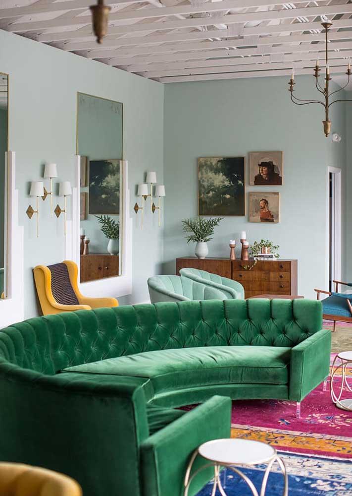 Sofá verde redondo, de veludo e com acabamento capitonê. Nada básico, não é mesmo?