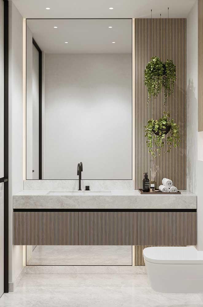 Bancada de mármore complementada pelo painel de madeira com plantas