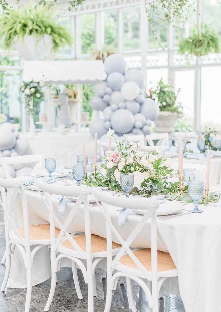 A mesa posta traz flores e louças combinando com a decoração do chá de bebê