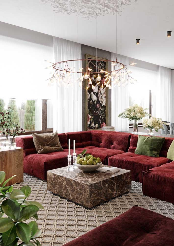 Já aqui, o modelo luxuoso de lustre redondo cobre todo centro da sala