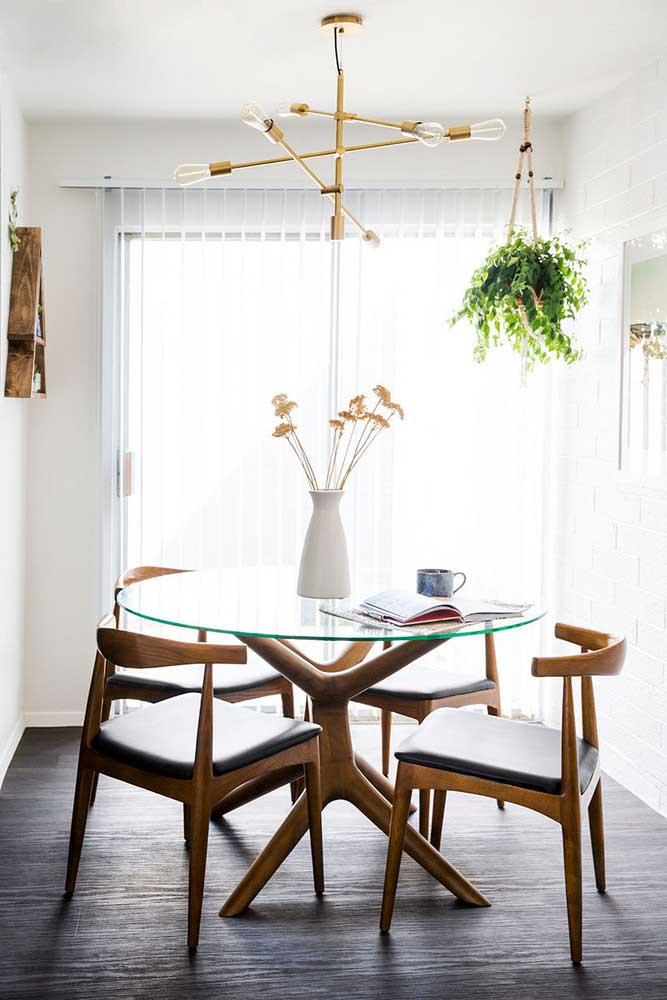 Aqui, a base de madeira da mesa de vidro tem a mesma forma orgânica das cadeiras