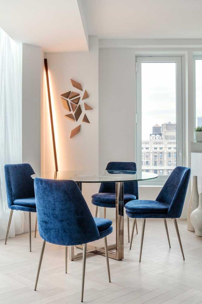 Já nessa sala moderna e clean, a mesa de vidro redonda apostou na base de inox