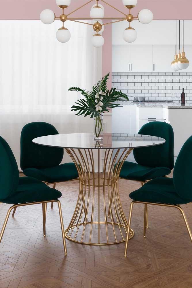 Mesa de vidro redonda quatro lugares com base dourada, assim como as cadeiras. Destaque para o estofamento luxuoso que fecha o conjunto