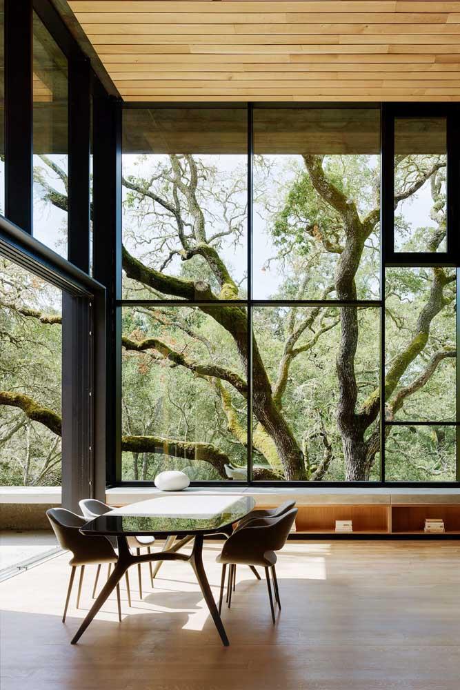 Que tal uma mesa de vidro com base de madeira combinando com o cenário que vem lá de fora?