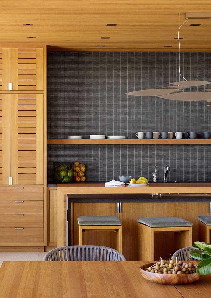 Revestimento de parede interno também pode ter cor escura. Aqui, as pastilhas cinzas são o destaque da cozinha