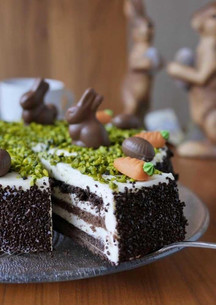 Bolo de páscoa de chocolate com cobertura simples de granulado e decorado com coelhinhos