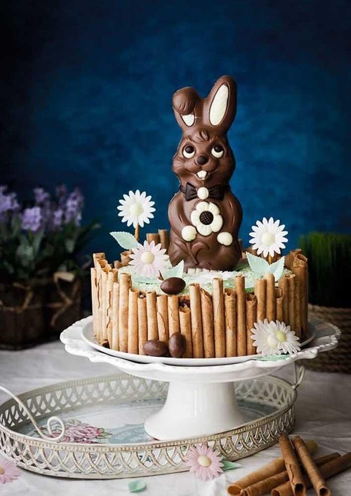 Bolo de páscoa decorado com um coelho de chocolate gigante. A cerquinha de canudinhos é outro destaque do bolo