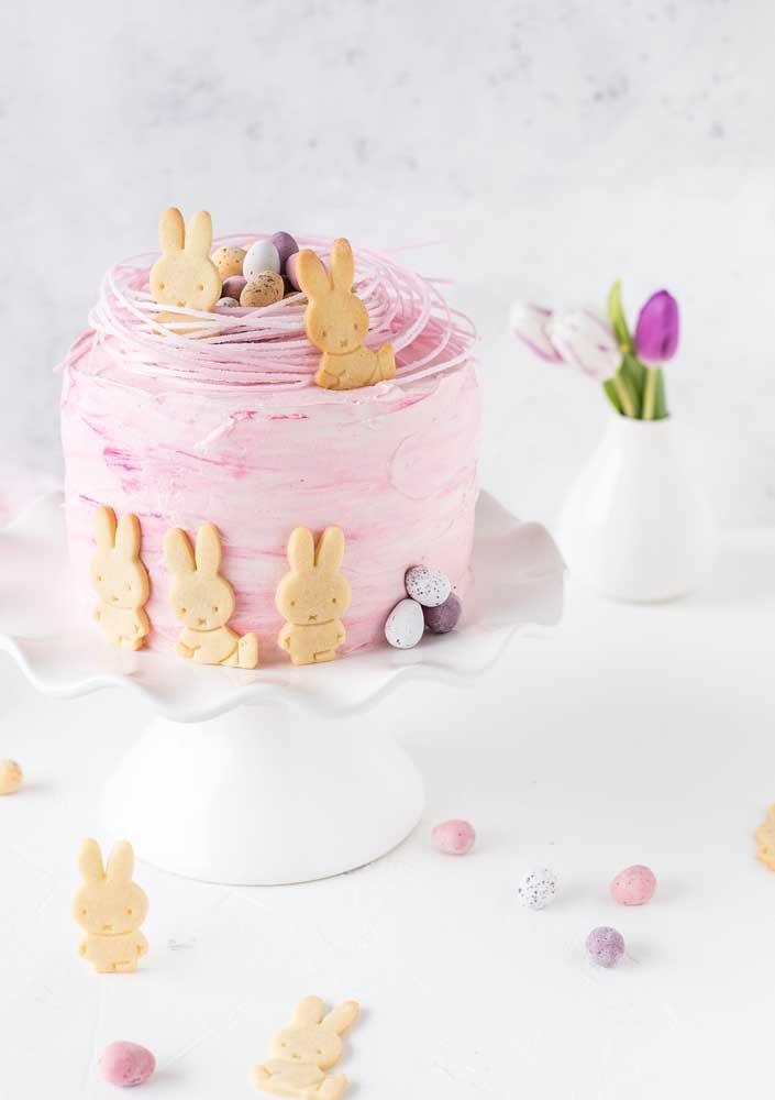 E o que acha de um bolo de páscoa de chantilly cor de rosa decorado com biscoitinhos de coelhos?